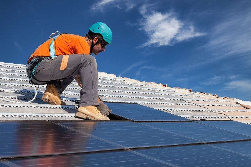 Man installing solar panels on a residential home